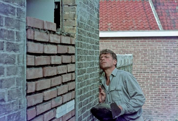 Gerard Reve keurt zijn metselwerk aan de linkerkant van Huize 'Het Gras'